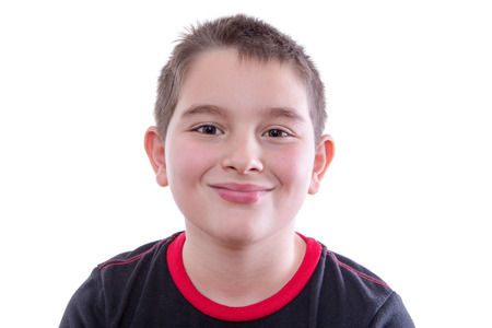 trustful: Head and Shoulders Close Up Portrait of Young Boy Wearing Red and Black T-Shirt and Smiling at Camera in Studio with White Background and Copy Space Stock Photo