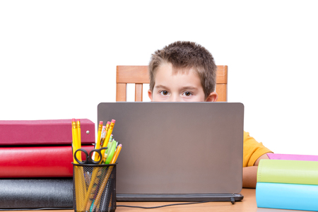 pencil holder: Young Boy Peeking Over Top of Laptop Computer Screen While Studying at Desk with Pencil Holder and Supplies and Surrounded by Colorful Books and Binders, in Room with White Background and Copy Space