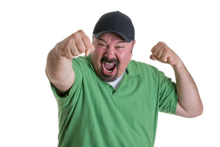 man with a goatee: Waist Up of Excited Man with Goatee Wearing Green Shirt and Baseball Cap Holding Fists in Air and Celebrating Team Win in Studio with White Background