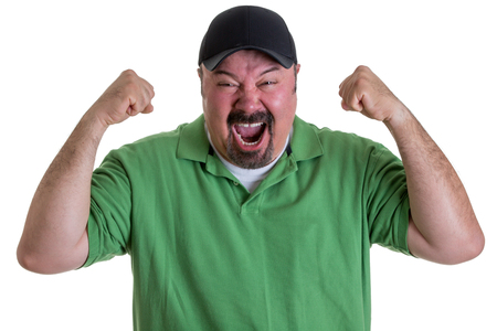 supporter: Waist Up of Excited Man with Goatee Wearing Green Shirt and Baseball Cap Holding Fists in Air and Celebrating Team Win in Studio with White Background