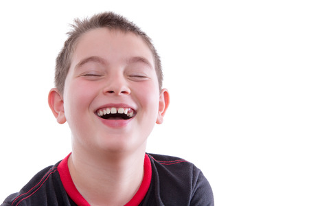 mirth: Head and Shoulders Close Up Portrait of Joyful Young Boy Wearing Red and Black T-Shirt and Laughing with Eyes Closed in Studio with White Background and Copy Space