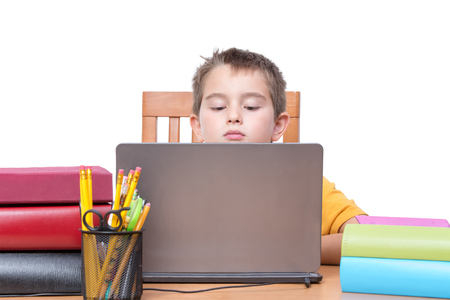 pencil holder: Young Boy Looking Down at Laptop Computer Screen While Studying at Desk with Pencil Holder and Supplies and Surrounded by Colorful Books and Binders, in Room with White Background and Copy Space Stock Photo