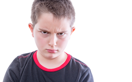 antagonistic: Head and Shoulders Close Up Portrait of Young Tween Boy Wearing Black and Red T-Shirt Frowning with Furrowed Brow at Camera in Studio with White Background and Copy Space