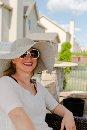 contented: Candid Waist Up Portrait of Smiling Woman Wearing Large Brimmed Sun Hat and Sunglasses Relaxing Outdoors on Wicker Patio Chair in Back Yard on Sunny Summer Day with Neighborhood Houses in Background