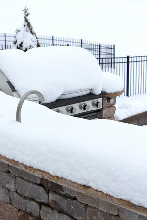 inclement: Detail of BBQ on Stone Patio Buried Beneath Heavy Snow in Winter - Disused Outdoor Kitchen Neglected Under Winter Snow in Back Yard of Home
