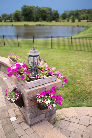 planters: Stone Pillar with Unlit Lamp Decorated with Bright Purple and White Garden Flowers Planted in Hanging Planters and Wooden Boxes, part of Wall Surrounding Luxury Patio with View of Small Lake