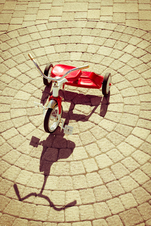 three wheeler: High Angle View of Red Vintage Tricycle in Bright Sunshine Casting Strong Shadow on Patio Stones Arranged in Circular Pattern Outdoors on Summer Day