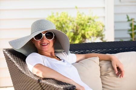 Candid Waist Up Portrait of Woman Wearing Large Brimmed Sun Hat and Sunglasses Relaxing Outdoors on Patio Love Seat with Comfortable Cushions in Back Yard on Sunny Summer Day