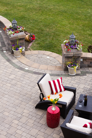 outdoor living: High Angle View of Luxury Patio with Outdoor Living Room Furniture and Stone Pillars Decorated with Colorful Flowers - Red Wine Served near Comfortable Chairs with Striped Cushions on Stone Patio