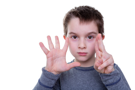 fingers: Cute serious little boy gesturing with seven fingers on two hands as if to count or display a symbol