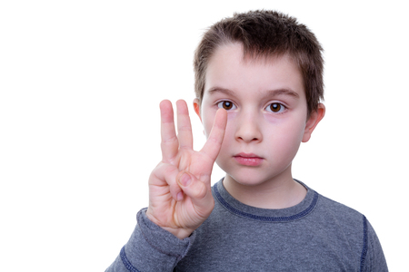 fingers: Close up of serious little boy gesturing with three fingers as if to count or display a symbol