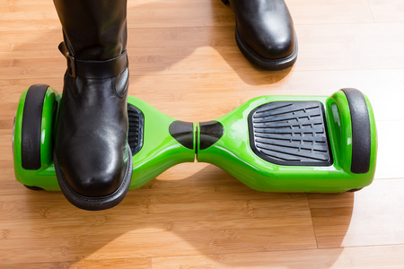 pies masculinos: Close up of hoverboard from front top view with one of the riders feet on top and the other on wooden floor