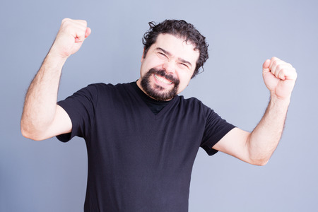 elated: Single handsome bearded man in black shirt holding fists up with elated expression over gray background