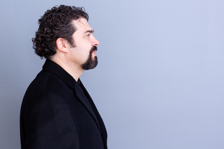 dark haired: Profile of calm handsome dark haired and bearded middle aged man wearing black shirt and blazer over gray background with copy space