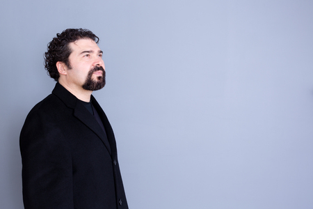 hope: Three quarter view of hopeful attractive dark haired and bearded middle aged male in black shirt and blazer looking away over gray background with copy space