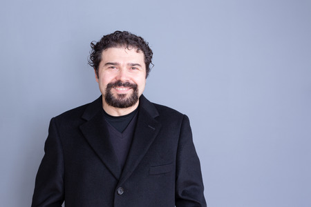 Single smiling handsome dark haired and bearded middle aged man wearing black shirt and blazer over gray background with copy space Stock Photo