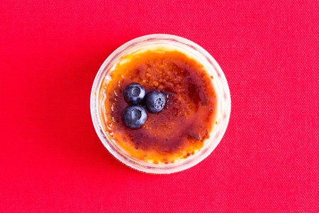 Freshly baked custard dessert topped with three blueberries from top view over red background Imagens