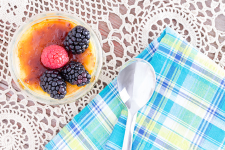 Delicious caramelized custard topped with red and black raspberries from point of view angle with spoon over doily and blue napkin