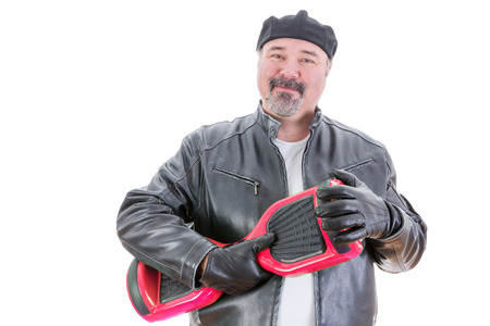 possessive: Content middle aged handsome man in hat and leather jacket stands holding a red and black hoverboard in hands with leather gloves