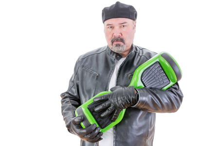 possessive: Rebellious middle aged man in leather jacket and gloves holding green and black hoverboard over white background Stock Photo
