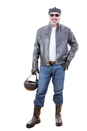 self assured: Tough handsome middle aged bearded man in motorcyclist outfit with boots holding helmet as he stands over white background smiling Stock Photo