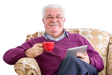 Cheerful senior male in purple sweater holding tablet computer in one hand and a red mug in the other while relaxing in chair over white background 版權商用圖片