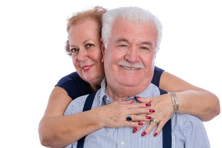Pair of older husband and wife in loving embrace with expression of a long life together over white background