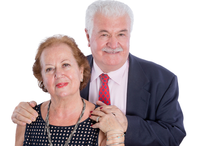 Smiling husband in blue suit with red tie standing behind his contented wife and holding her hand over white background Stock Photo