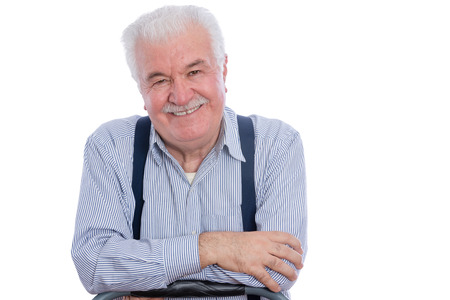the distinguished: Cute senior man with mustache in white striped shirt and blue suspenders with joyful expression and folded arms over white background