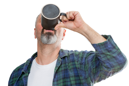 early fifties: Single middle aged bearded man in flannel and tee shirt gulping down the last drop of coffee from a dark mug over white background