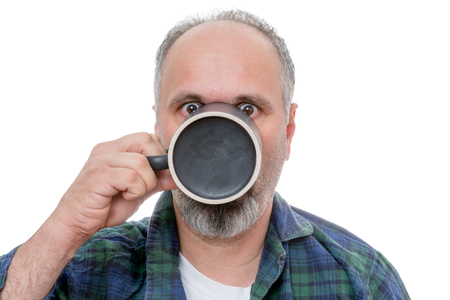 Single balding and bearded shocked man drinking from a dark coffee mug with wide open eyes over white background Stock Photo