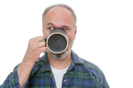 quizzical: Single balding middle aged bearded man drinking from mug in front of his mouth as he looks over to his side on white background Stock Photo