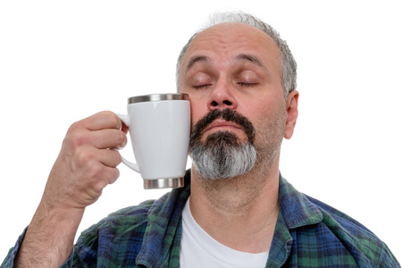 somnolent: Sleepy middle aged man with receding hairline and beard struggling to bring a coffee mug to his mouth after awakening