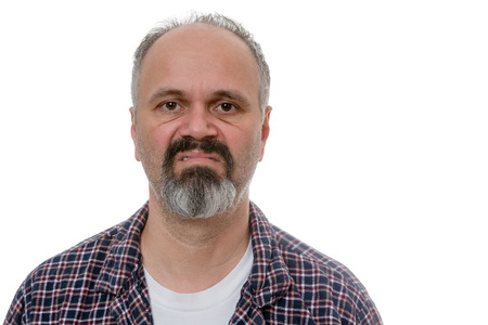 early 40s: Single balding grumpy old man in beard, mustache and plaid pyjamas with angry expression over white undershirt Stock Photo
