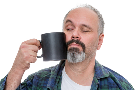 quizzical: Waking middle aged man dressed in flannel shirt and pajamas and receding hairline with beard tries to drink from a dark coffee mug Stock Photo