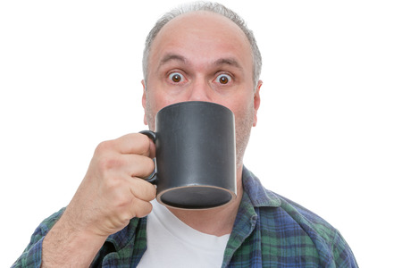 balding: Single balding and bearded shocked man holding dark coffee mug in front of face with wide open eyes over white background