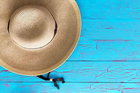 a straw: Wide brimmed straw gardening hat on an old weathered colorful blue picnic table with copy space in an overhead view Stock Photo