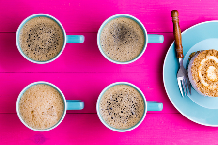 regimented: Vibrant overhead image of coffee and cake with four aligned blue cups of frothy black espresso coffee with their handles pointing to chocolate swiss roll cake on a plate on a vivid pink background Stock Photo