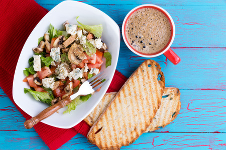 energising: Fresh mixed feta salad on a platter served with frothy espresso coffee and toasted baguette on a colorful tropical blue picnic table with copy space viewed from above