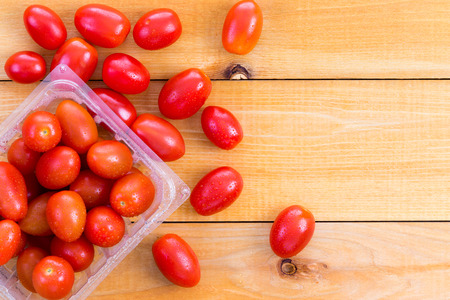 spread around: Punnet of fresh healthy baby tomatoes displayed on a wooden table with some spread around alongside , copy space to the side Stock Photo