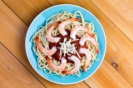 garnish: Savory Italian seafood pasta with peeled shrimps on a bed of spaghetti with a tomato sauce and grated gruyere cheese garnish, overhead view on a blue plate on a picnic table Stock Photo