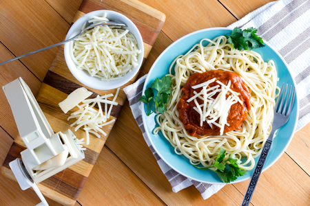 spaghetti: Top down first person perspective view on round plate of freshly cooked spaghetti topped with red sauce, parsley and grated gruyere cheese next to pasta press on cutting board Stock Photo