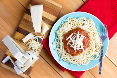 red cooked: Top down first person perspective view on round plate of freshly cooked spaghetti topped with red sauce and grated gruyere cheese next to pasta press on cutting board