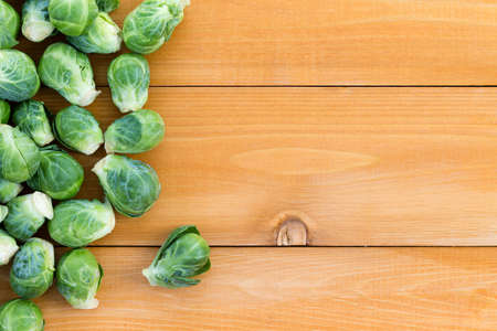 sprouts: Fresh farm brussels sprouts arranged to the side on a wooden garden table, overhead with copy space