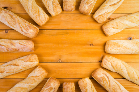 crusty french bread: Circular frame of freshly baked crusty French bread loaves arranged in a radiating circle over a wooden table with central copy space, viewed from above