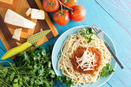 queso rallado: Vista desde arriba de un solo plato de espaguetis recién preparados con salsa roja, el perejil y el queso gruyere junto a un cuchillo en la tabla de cortar con tomates cherry sobre tabla azul