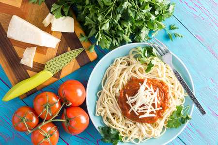 food still: View from above on round plate of freshly prepared spaghetti topped with red sauce, parsley and gruyere cheese beside knife on cutting board with cherry tomatoes Stock Photo