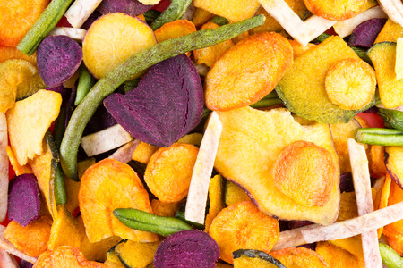 dried: Background food texture of organic healthy veggie chips made form an assortment of colorful dried sliced vegetables in a full frame view
