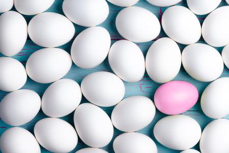 uno: Gran número de huevos de Pascua blancos recubiertos de azúcar con uno rosa entre ellos se muestra como una capa sobre una mesa azul, imagen conceptual en una vista de cuadro completo Foto de archivo