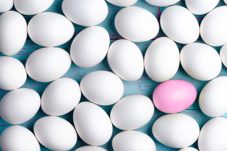 one: Large number of sugar-coated white Easter eggs with one pink one amongst them displayed as a layer on a blue table, conceptual image in a full frame view